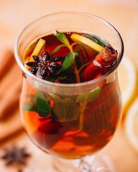 Seitenansicht des glühweins mit zimtanis und orange in einem glas
