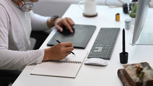 Seitenansicht des grafikdesigners, der zu hause an einem tisch sitzt und am computer arbeitet und ideen in einem notizbuch aufschreibt