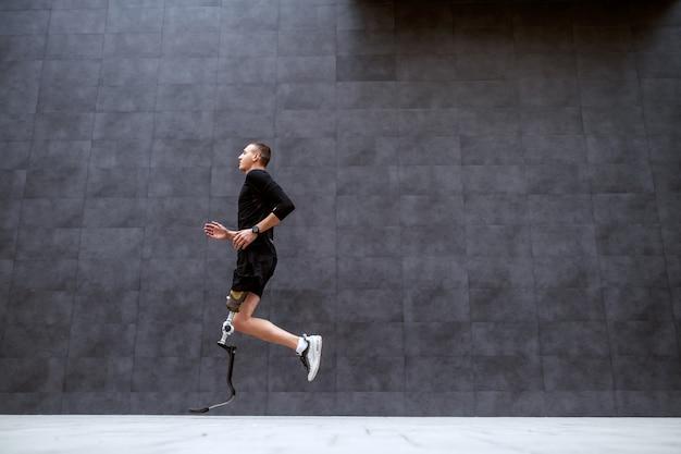 Seitenansicht des gutaussehenden kaukasischen sportlers mit künstlichem bein, das außerhalb läuft.