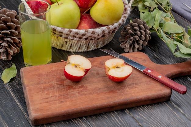 Seitenansicht des halbgeschnittenen apfels und des messers auf schneidebrett mit apfelsaftkorb von äpfeln tannenzapfen und blättern auf holzoberfläche