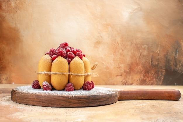 Seitenansicht des hausgemachten weichen kuchens mit früchten auf hölzernem schneidebrett auf gemischtem farbtisch