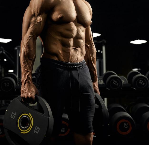 Seitenansicht des hemdlosen angespannten inkognito männlichen bodybuilders, der gewichte in den armen hält.
