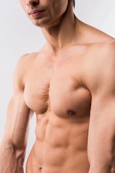 Seitenansicht des hemdlosen athletischen mannes, der körper mit muskeln vorführt