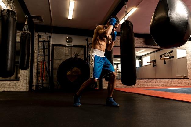 Seitenansicht des hemdlosen männlichen boxertrainings