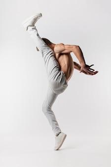 Seitenansicht des hemdlosen männlichen tänzers in den jeans und in turnschuhen, die mit dem bein oben aufwerfen