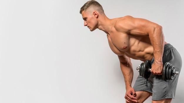 Seitenansicht des hemdlosen mannes, der mit gewicht und kopienraum ausarbeitet