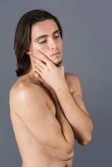 Seitenansicht des hemdlosen mannes mit make-up