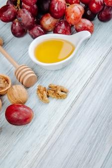 Seitenansicht des honigs mit hölzernem honiglöffel, frischen trauben und walnüssen auf grauem holztisch