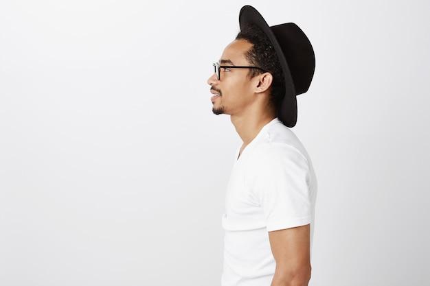 Seitenansicht des hübschen afroamerikanischen hipster-kerls im hut und in den gläsern, die links schauen