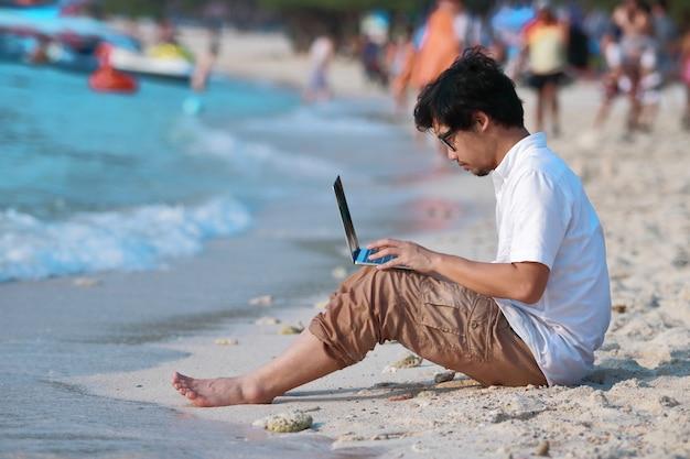 Seitenansicht des hübschen jungen asiatischen mannes, der laptop auf dem strand verwendet.