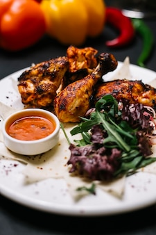 Seitenansicht des hühnerkebabs auf lavash, serviert mit frischen kräuterzwiebeln und adjika-sauce