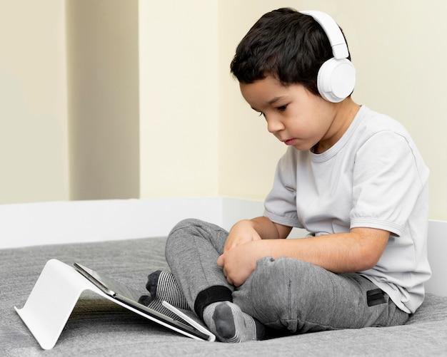 Seitenansicht des jungen, der tablette im bett mit kopfhörern verwendet