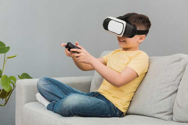 Seitenansicht des jungen, der videospiele mit virtual-reality-headset spielt