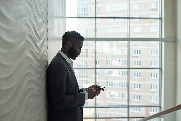 Seitenansicht des jungen ernsten afrikanischen geschäftsmannes in der formellen kleidung, die nahe an der wand steht, während im smartphone gegen fenster scrollen