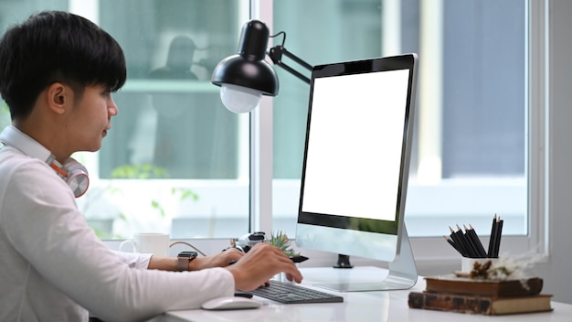 Seitenansicht des jungen männlichen freiberuflers, der mit computer zu hause büroraum arbeitet