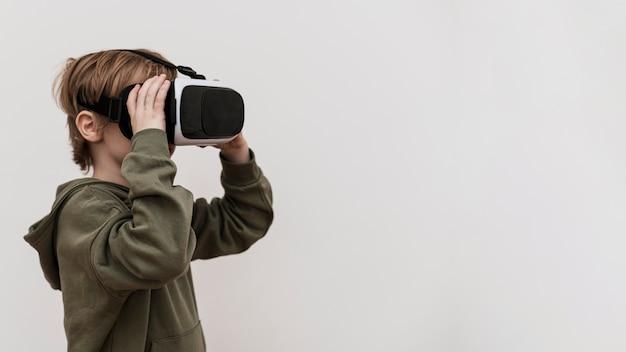 Seitenansicht des jungen unter verwendung des virtual-reality-headsets mit kopierraum