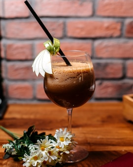 Seitenansicht des kaffeecocktails mit schnaps und sahne auf einem holztisch