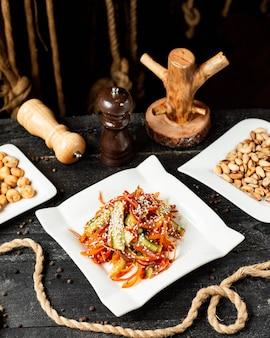 Seitenansicht des karottensalats mit gurkenpaprika und sesam auf teller