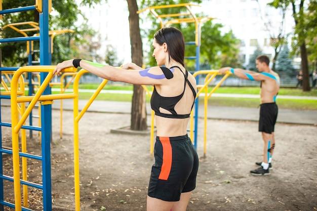 Seitenansicht des kaukasischen athletenpaares mit kinesiologischem elastischem taping auf körpern