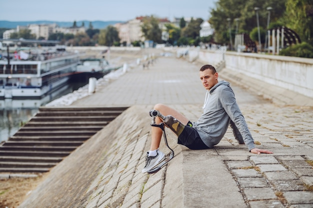 Seitenansicht des kaukasischen behinderten sportlers in sportbekleidung und mit künstlichem bein, das auf kai sitzt und wegschaut.