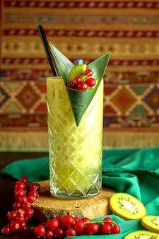 Seitenansicht des kiwi-smoothie im glas verziert mit frischer roter johannisbeere