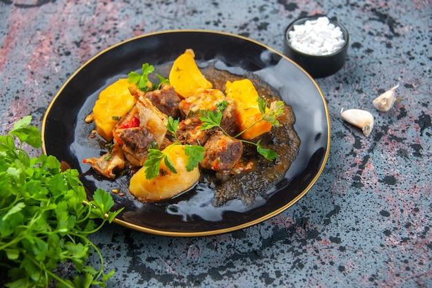 Seitenansicht des köstlichen abendessens mit fleischkartoffeln, die mit grün in einem schwarzen teller und knoblauchsalz auf mischfarbenhintergrund serviert werden