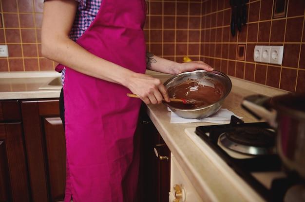 Seitenansicht des konditors in der rosa schürze, die geschmolzene schokoladenmasse in der schüssel mit einem hölzernen spatel mischt, der in ihrer hausküche steht