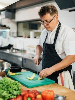 Seitenansicht des küchenchefs, der gemüse schneidet