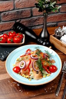 Seitenansicht des lachssalats mit rotem zwiebelkohl und körnern, die mit dill im teller auf holztisch gekrönt werden