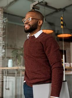 Seitenansicht des lächelnden mannes, der einen laptop hält