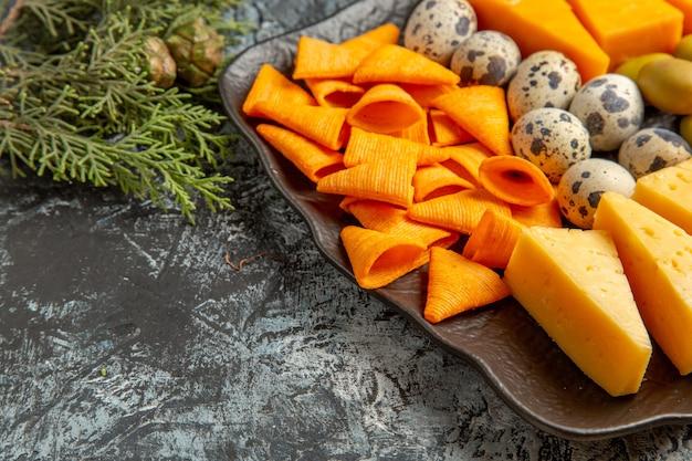 Seitenansicht des leckeren besten snacks für wein auf braunem tablett und tannenzweigen auf eishintergrund