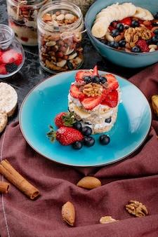 Seitenansicht des leckeren knäckebrots mit reifen blaubeeren, erdbeeren und nüssen mit saurer sahne auf einer keramikplatte auf rustikalem holztisch