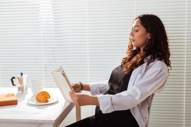 Seitenansicht des lesebuchs der schwangeren frau beim frühstück am morgen mit kaffee