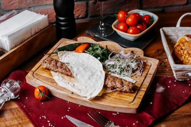 Seitenansicht des lula kebab mit zwiebeln, kräutern und gemüse auf einem holzbrett