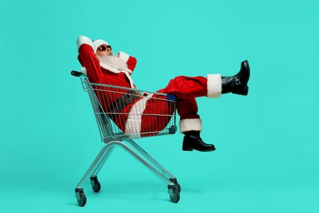 Seitenansicht des lustigen weihnachtsmannes in den schwarzen sonnenbrillen- und kostümherstellungsgesichtern. alter mann, der spaß hat, im einkaufswagen sitzt und sich entspannt