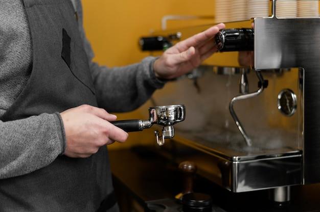 Seitenansicht des männlichen barista mit schürze unter verwendung der professionellen kaffeemaschine