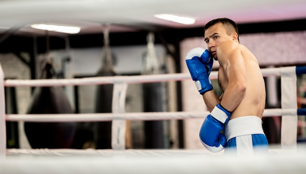 Seitenansicht des männlichen boxers, der im ring übt