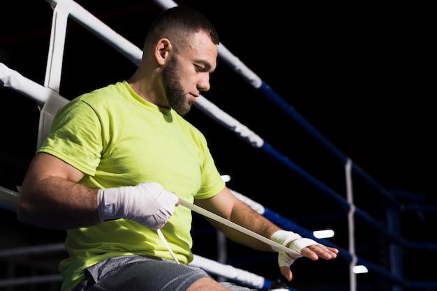 Seitenansicht des männlichen boxers im t-shirt, das auf schutz für hände mit kopienraum sich setzt