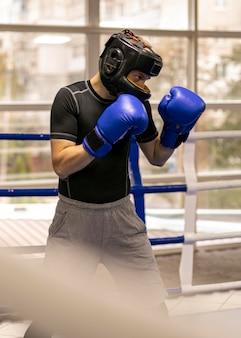 Seitenansicht des männlichen boxers mit handschuhen und helmtraining