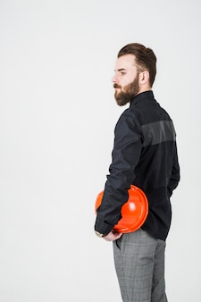 Seitenansicht des männlichen ingenieurs den hardhat halten, der gegen weißen hintergrund steht