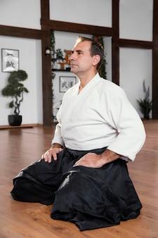 Seitenansicht des männlichen kampfkunstlehrers, der in der übungshalle sitzt
