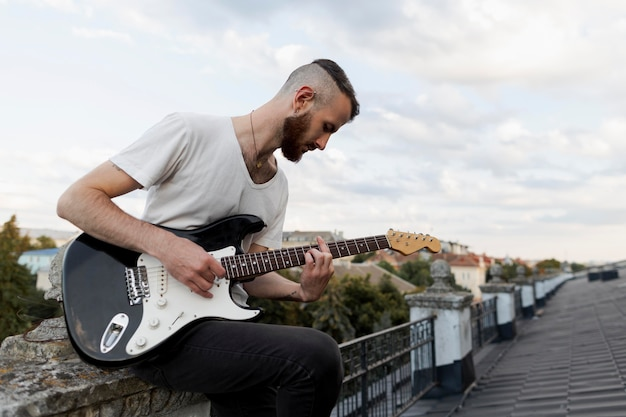 Seitenansicht des männlichen künstlers auf dem dach, der e-gitarre spielt