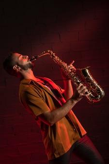 Seitenansicht des männlichen künstlers, der das saxophon spielt