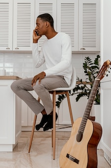 Seitenansicht des männlichen musikers, der am telefon neben der gitarre spricht