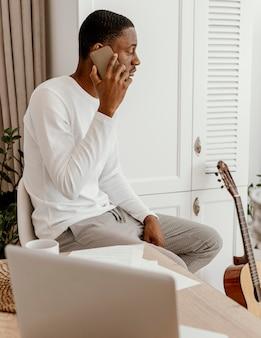 Seitenansicht des männlichen musikers, der auf dem smartphone neben der gitarre spricht