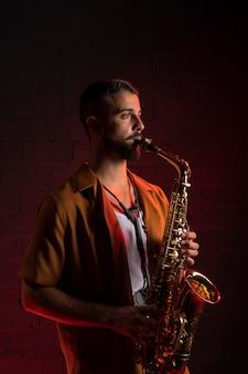 Seitenansicht des männlichen musikers, der das saxophon spielt