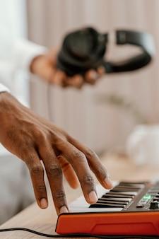 Seitenansicht des männlichen musikers, der elektrische tastatur spielt und kopfhörer hält