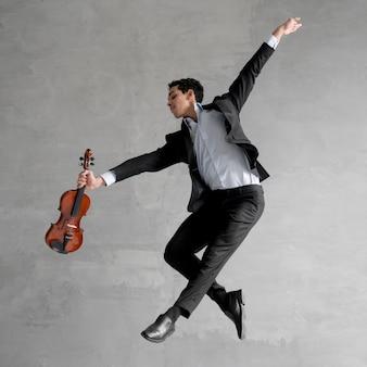 Seitenansicht des männlichen musikers, der geige hält und mitten in der luft aufwirft