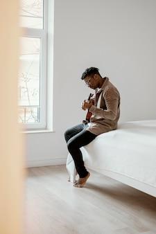Seitenansicht des männlichen musikers, der gitarre auf bett spielt