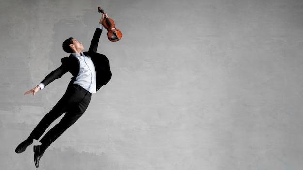 Seitenansicht des männlichen musikers, der mitten in der luft aufstellt, während geige hält